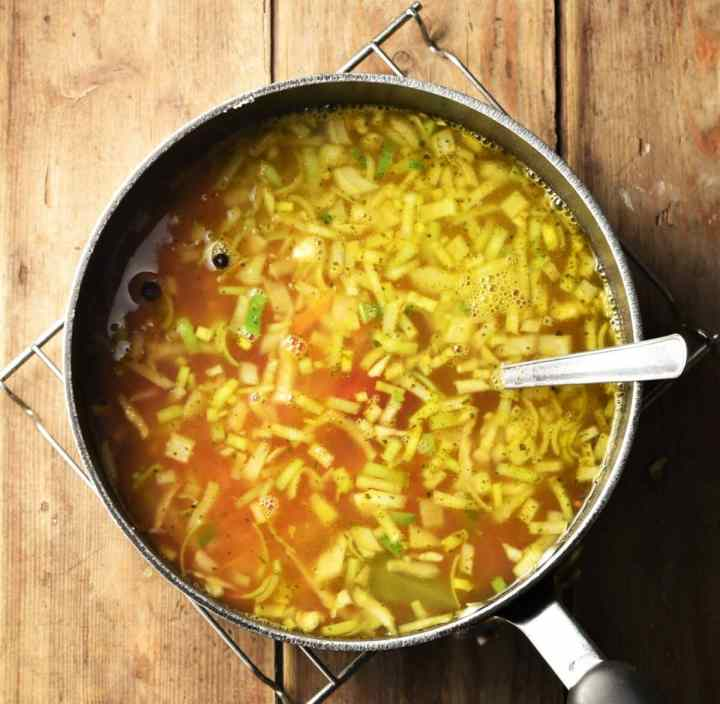 Chopped vegetables in tomato soup in large pot with spoon.