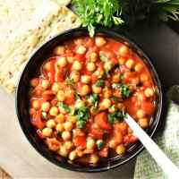 Chickpea stew in black bowl with spoon, fresh parsley and pita in background.