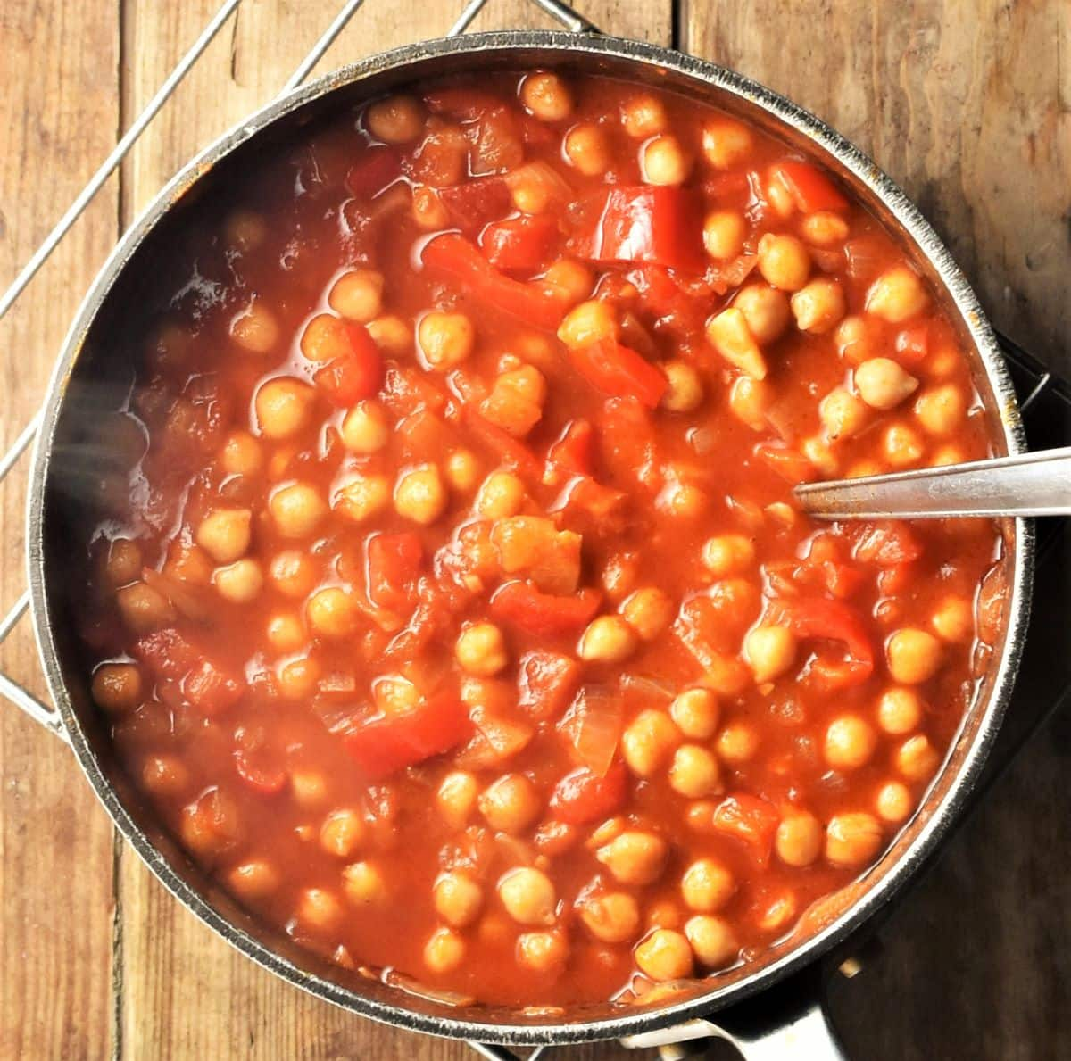 Chickpea casserole in pot with spoon.