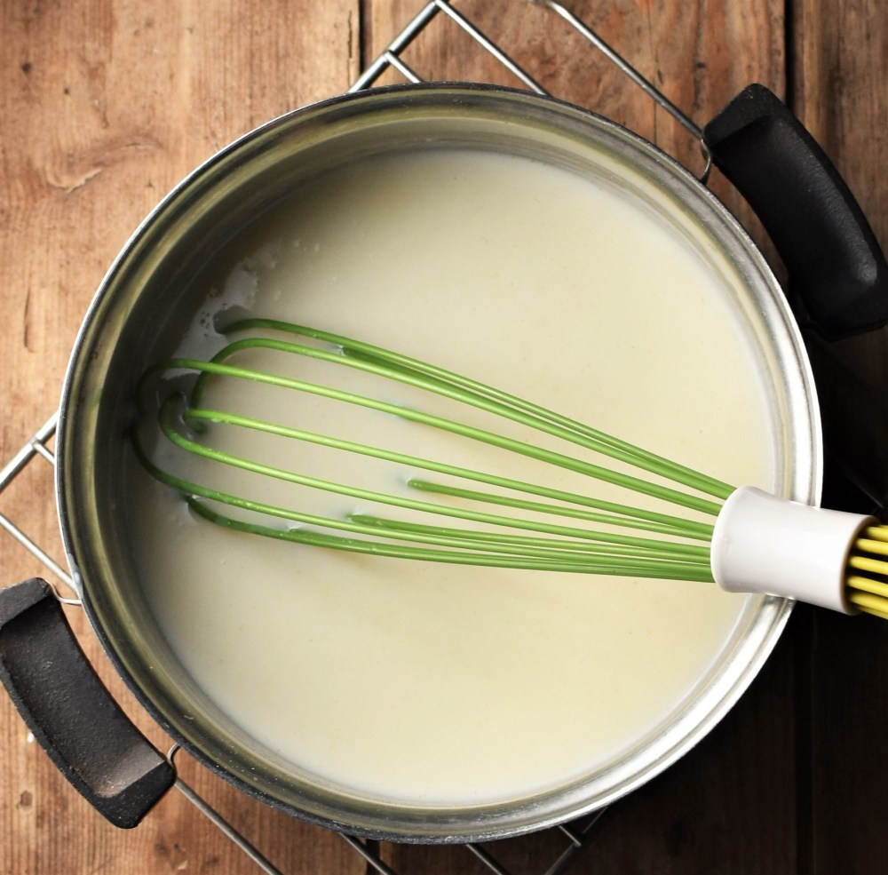 Bechamel sauce in saucepan with green whisk.