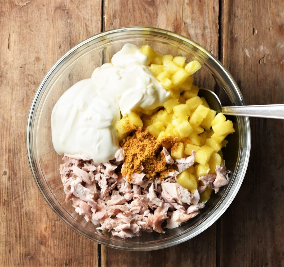 Chopped chicken, pineapple, yogurt and spice in mixing bowl with spoon.