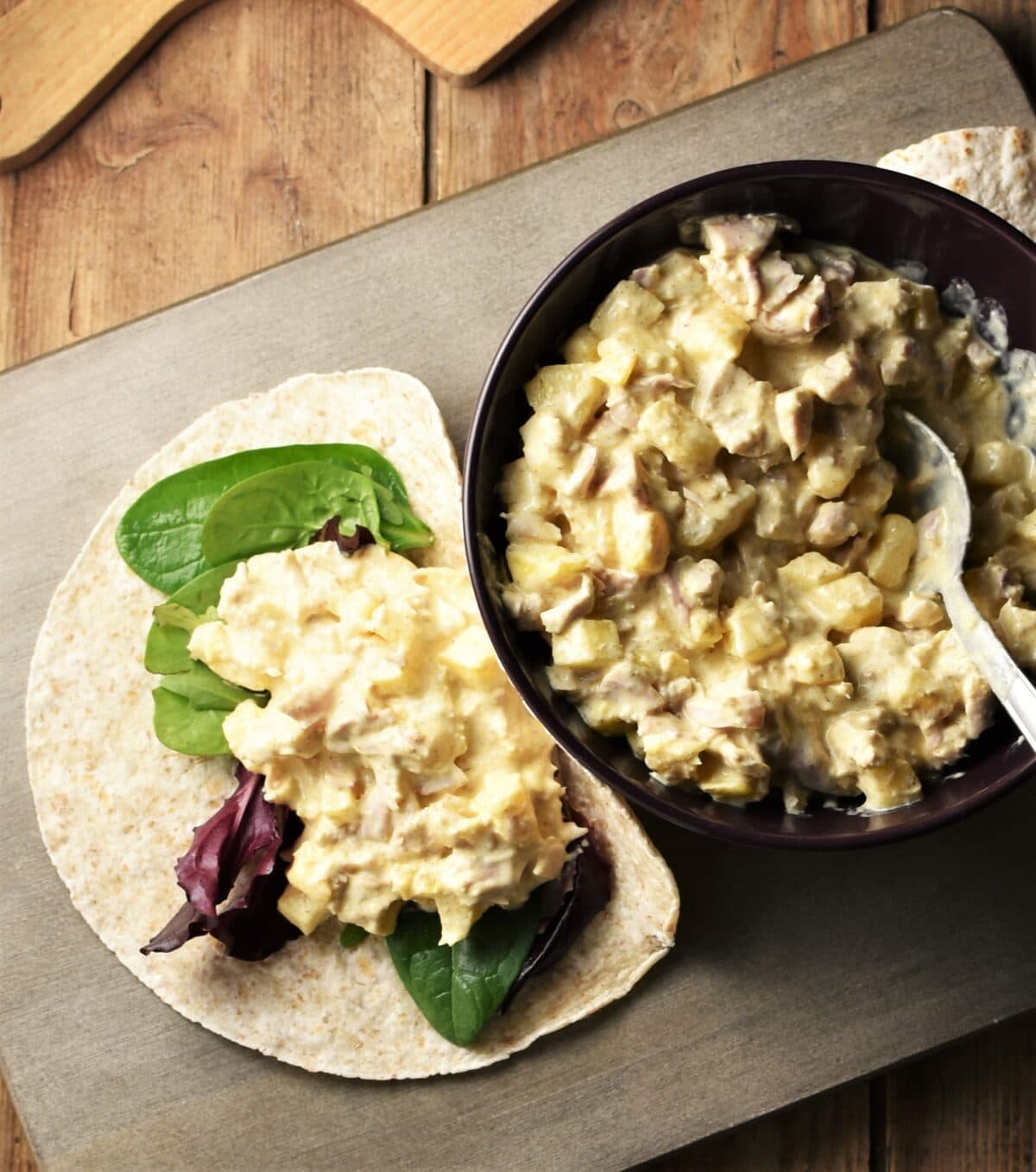 Chicken pineapple salad on top of wrap and in purple bowl with spoon.
