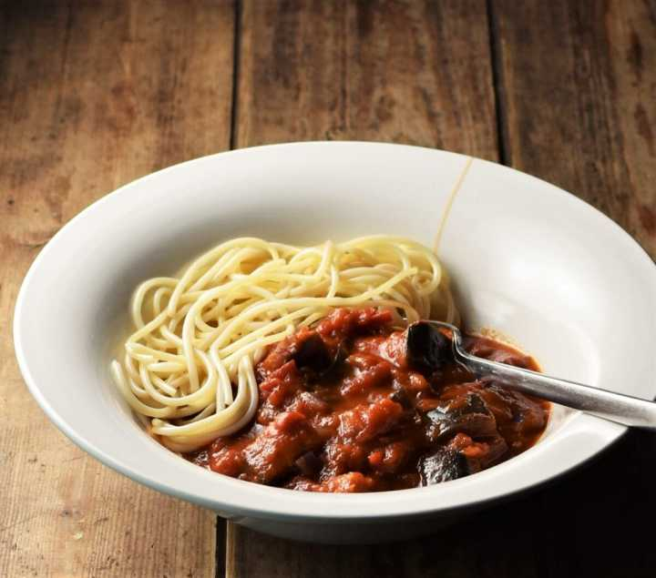 Eggplant tomato sauce with spaghetti in white bowl with fork.