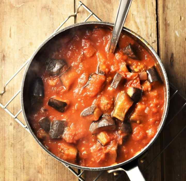 Top down view of eggplant and tomato sauce in large pot with spoon.