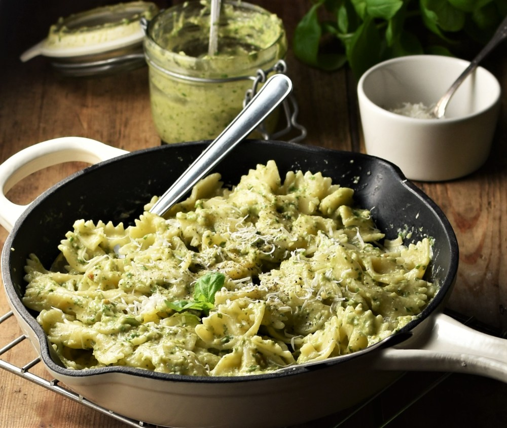 Side view of pasta with pesto in skillet, with pesto in jar in background.
