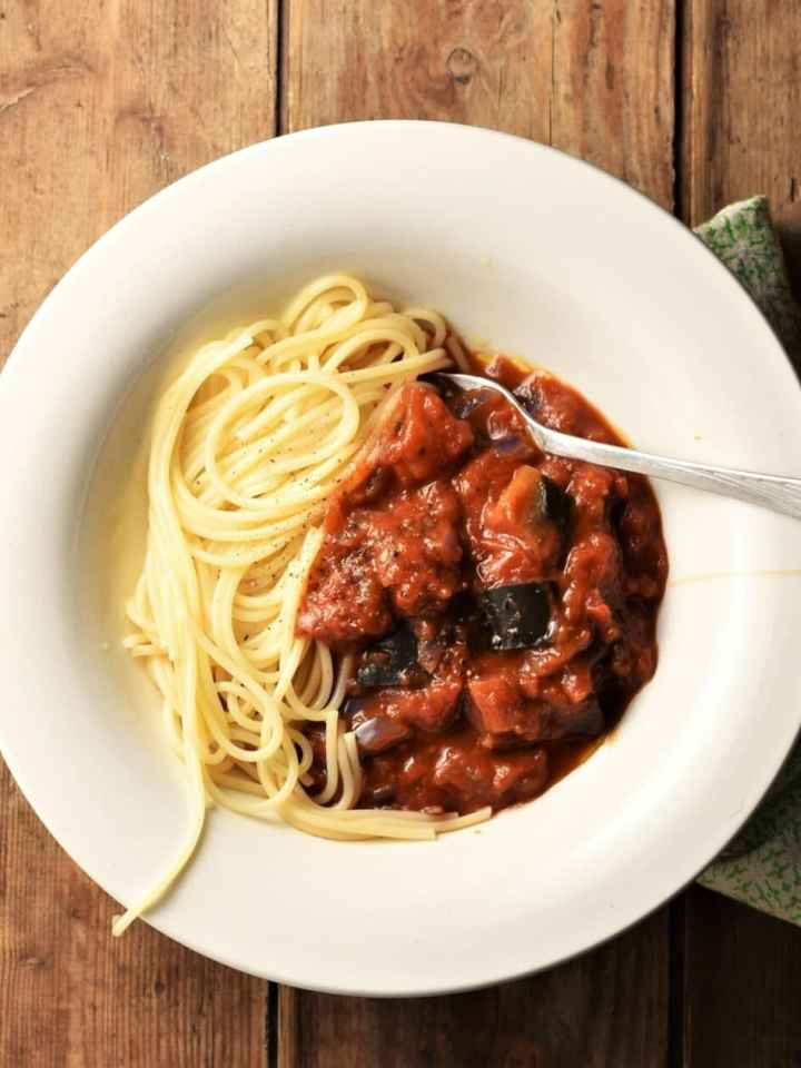 Chunky eggplant tomato sauce with spaghetti in white bowl with fork.