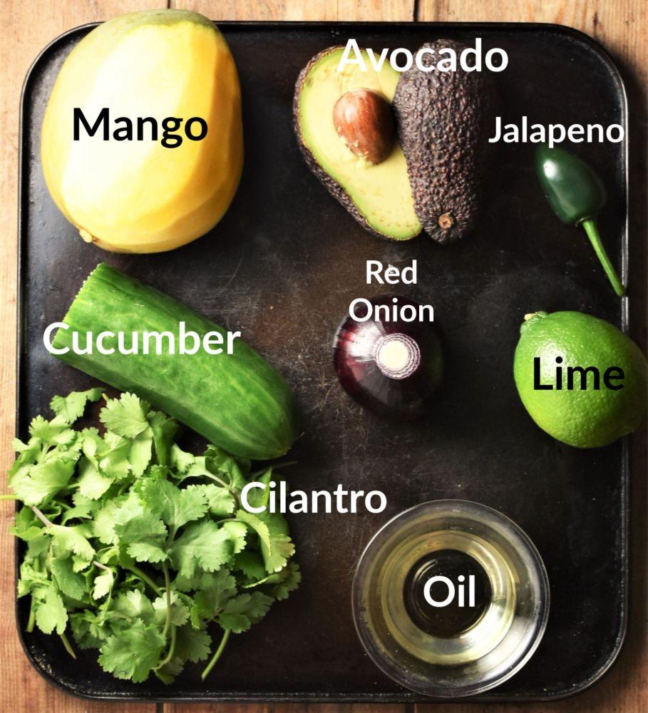 Avocado mango cucumber salsa ingredients on top of dark tray.