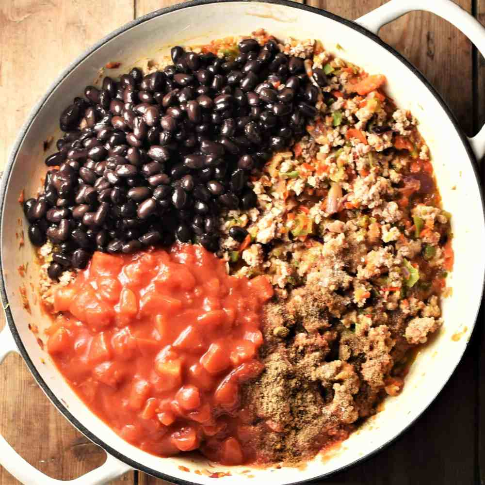 Black beans, chopped tomatoes and meat mixture in large white pan.