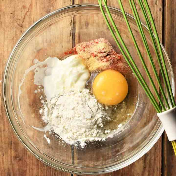 Flour, egg, yogurt and spices in mixing bowl with green whisk.