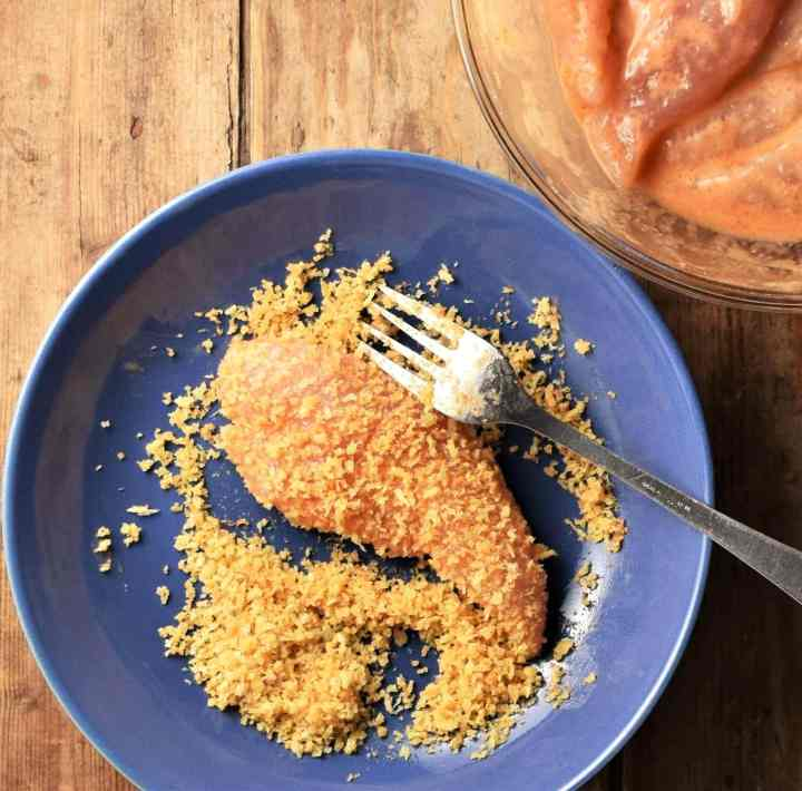 Breaded chicken finger in blue bowl with fork.