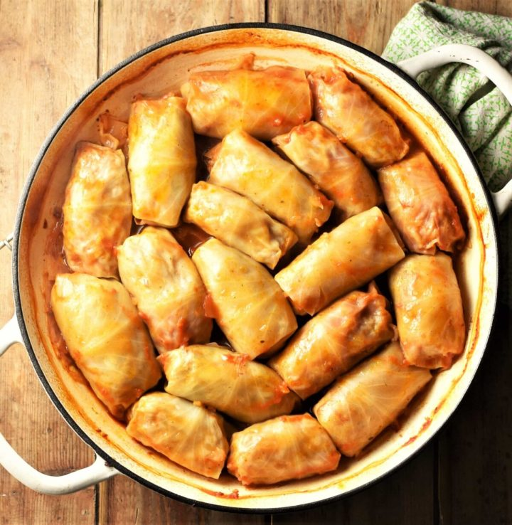 Top down view of cabbage rolls in large white shallow pan.