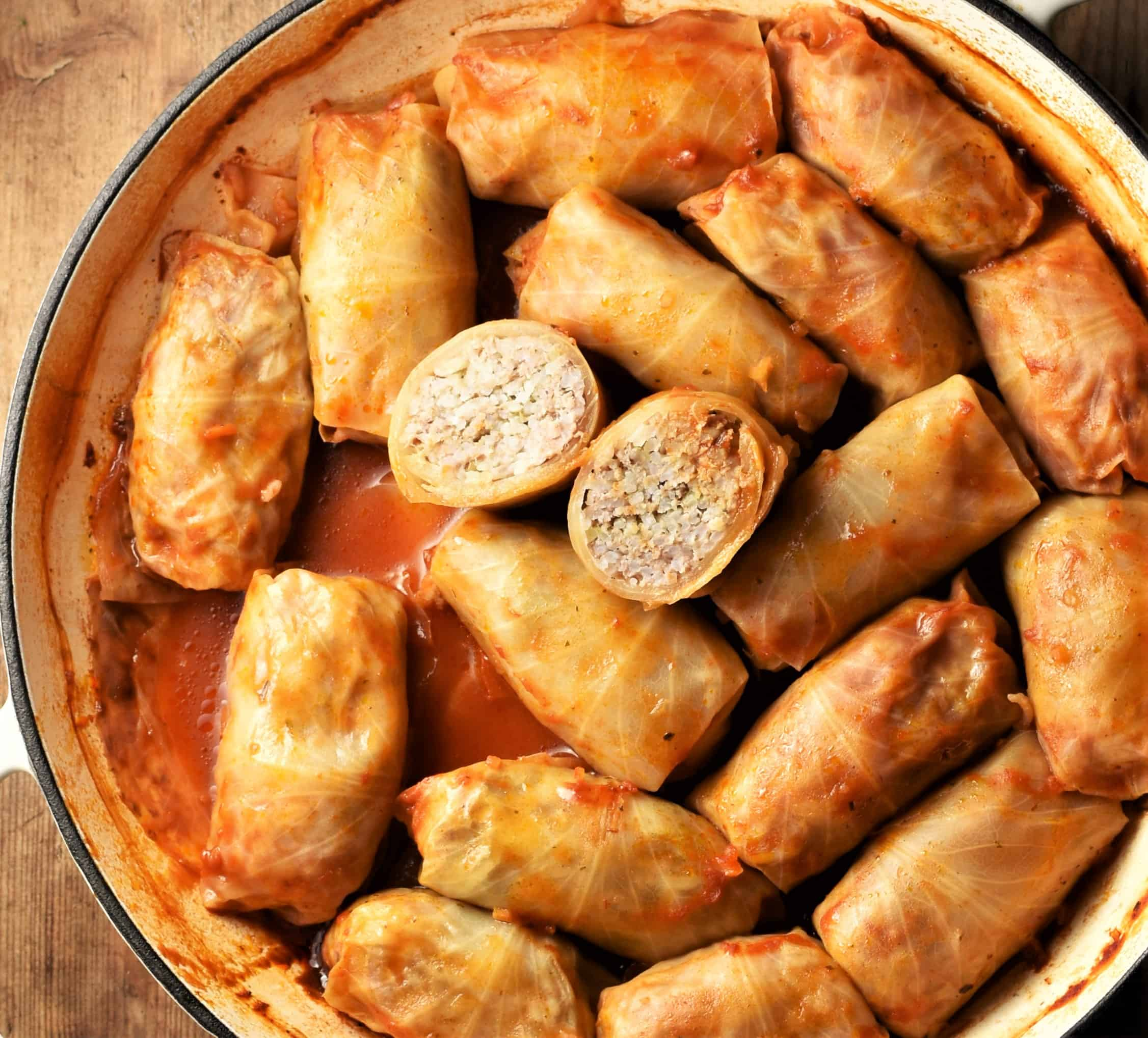 Top down view of cabbage rolls in tomato sauce in large white shallow pan.
