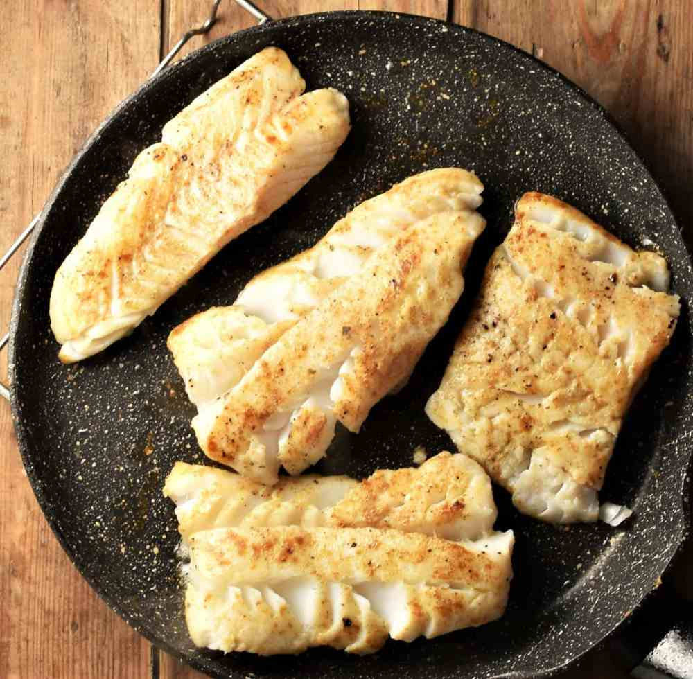 4 large fish fillets in frying pan.