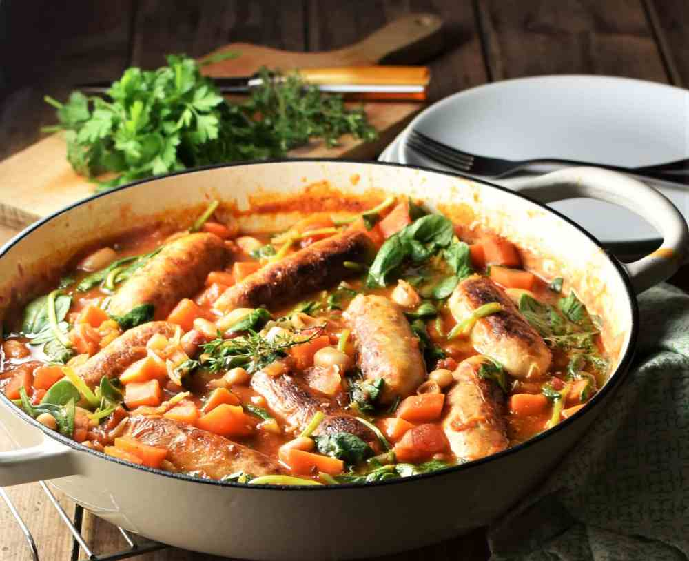 Side view of bean sausage casserole with spinach in white pan, with herbs and plates in background.