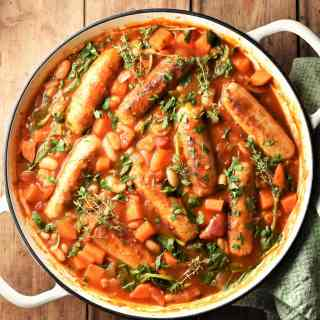 Sausage and bean casserole with vegetables and herbs in large white pan.