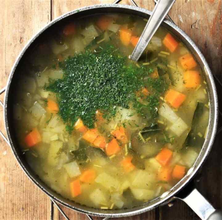 Chunky vegetable soup with fresh dill in pot with spoon.