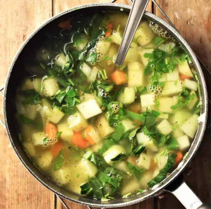 Chunky kohlrabi and vegetable soup in pot with spoon.