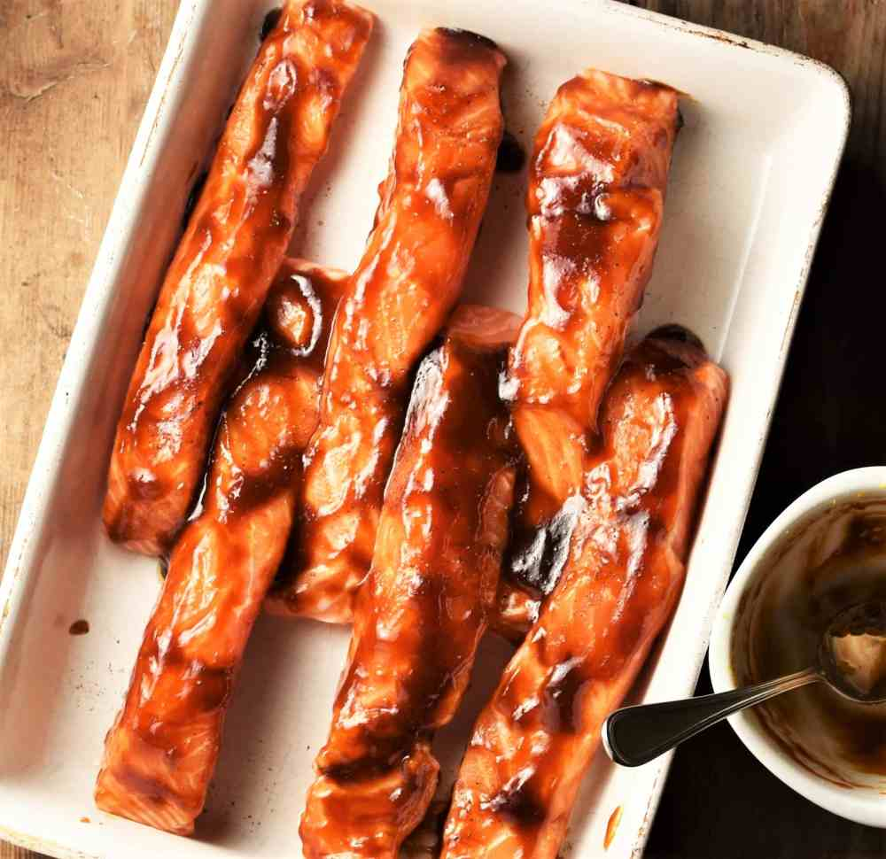 Top down view of salmon strips in hoisin marinade in white shallow dish.