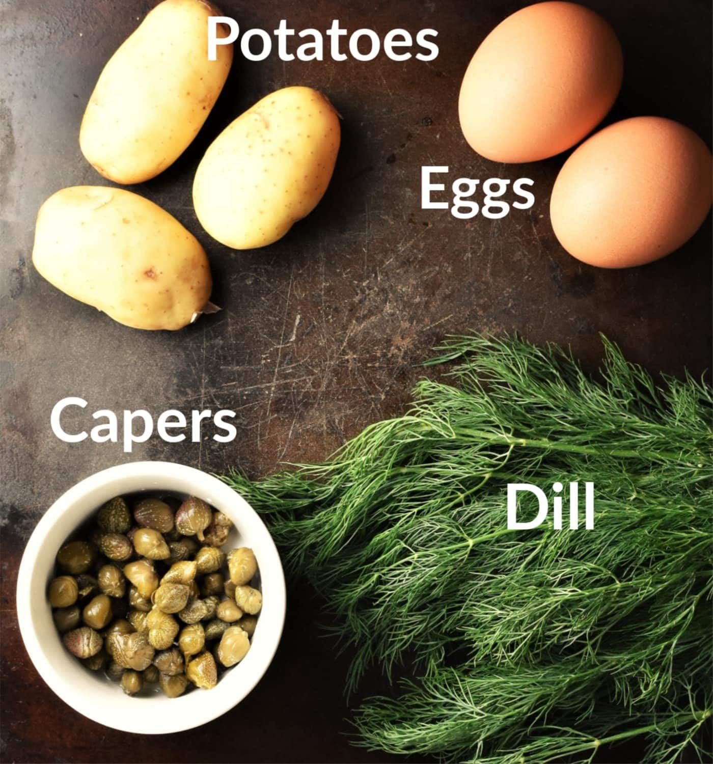 Potato dill salad ingredients on top of black surface.
