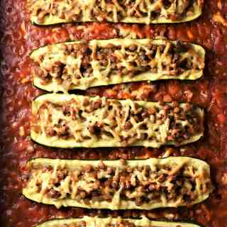 Baked vegetarian lentil stuffed zucchini in tomato sauce.