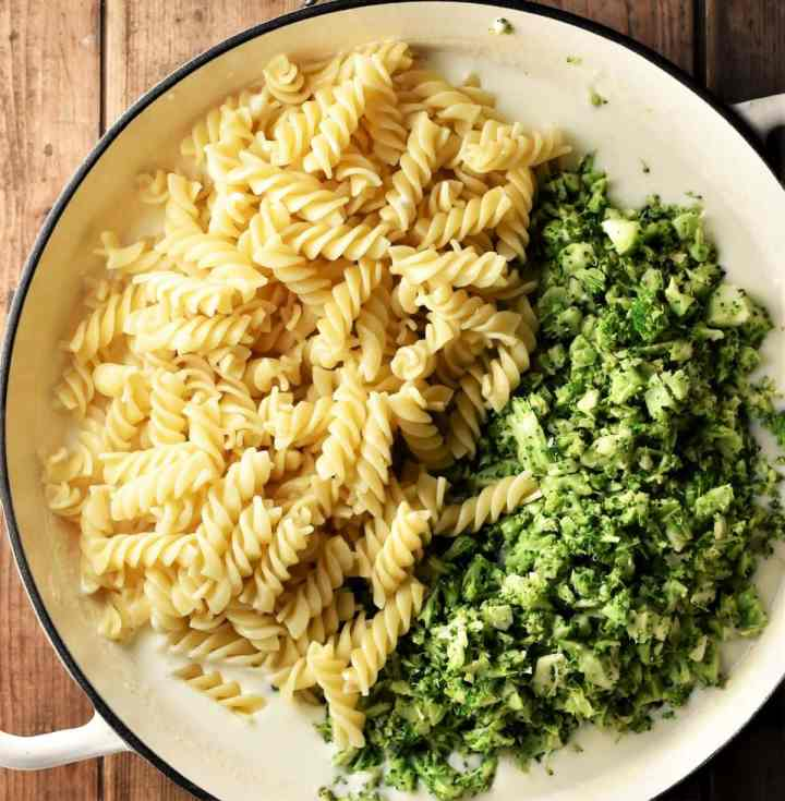 Fusilli pasta and broccoli rice in large shallow pan.