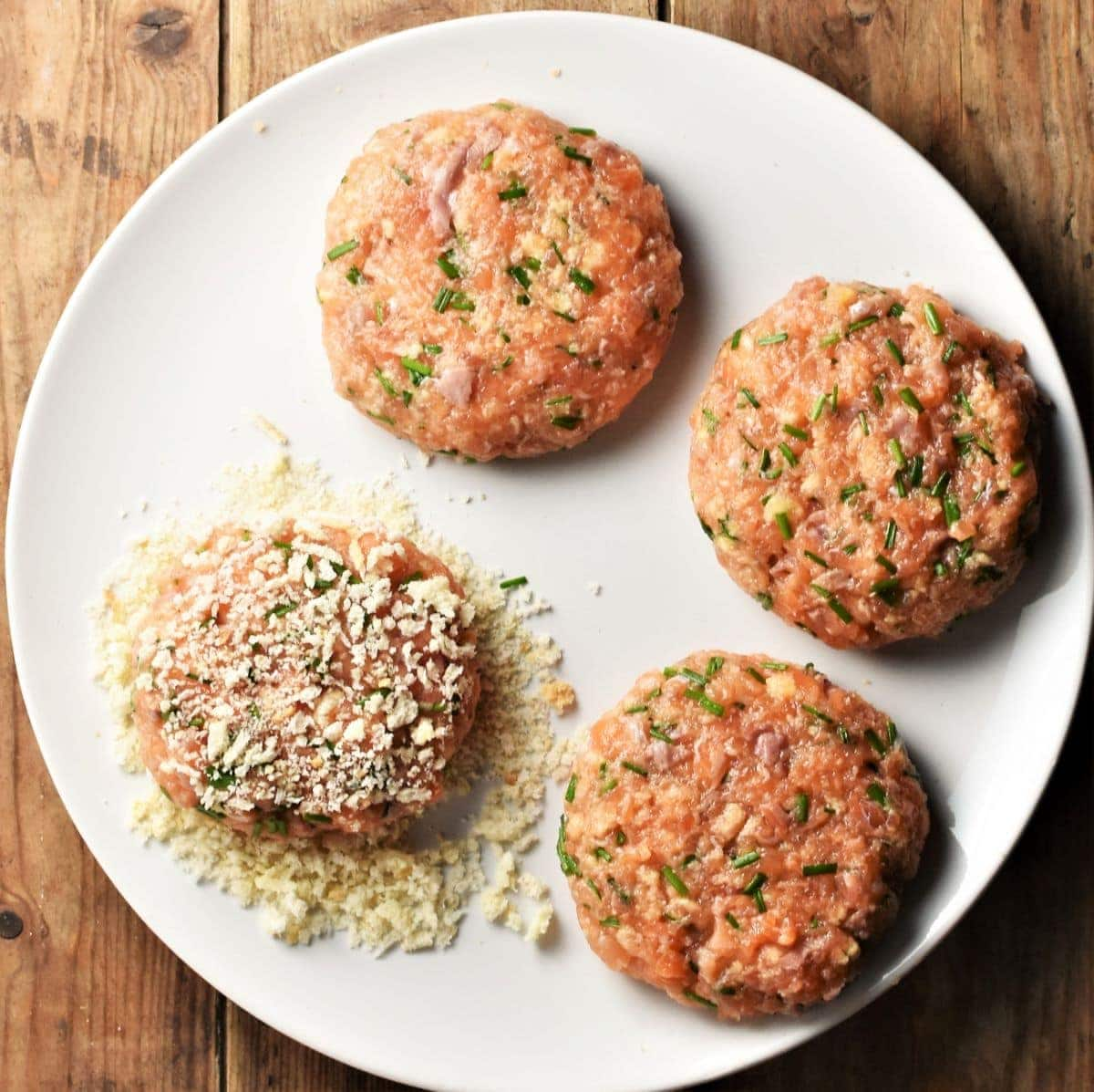 4 salmon burgers with breadcrumbs on large plate.