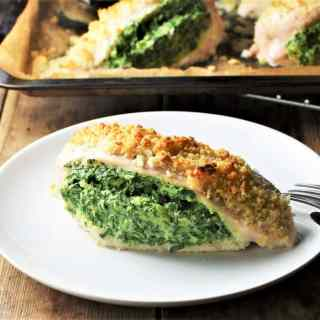 Side view of spinach and cheese stuffed chicken breast on top of plate with chicken in background.