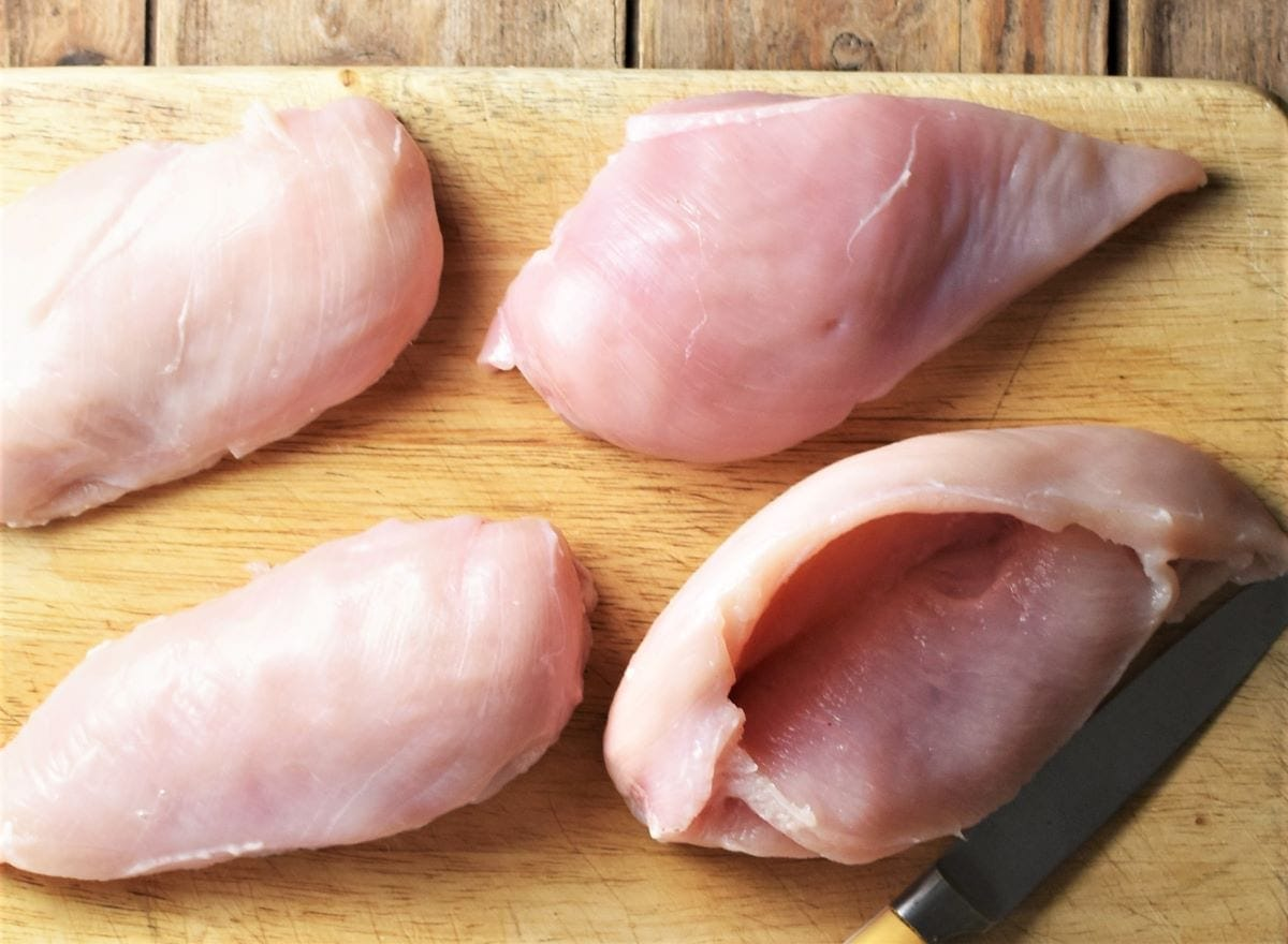 4 raw skinless chicken breasts on top of cutting board with knife.