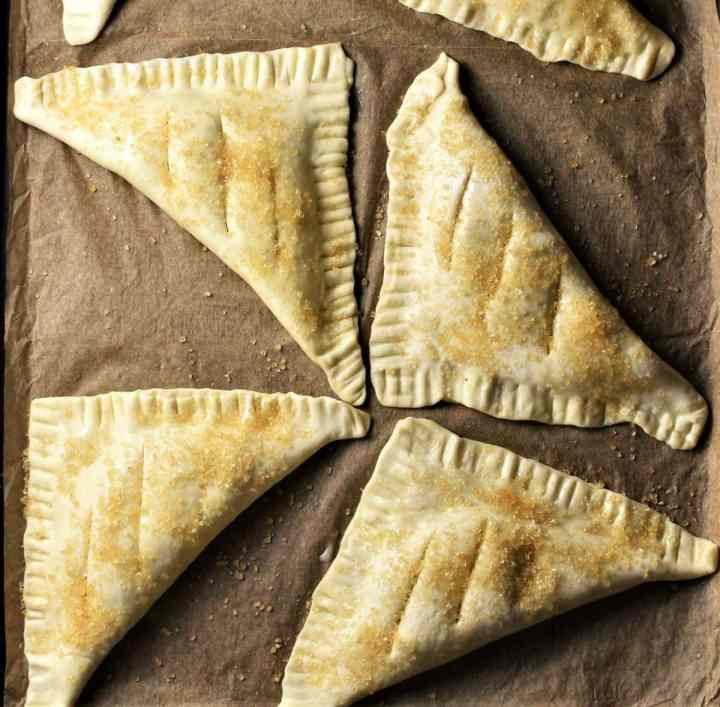 Unbaked turnovers on top of parchment.