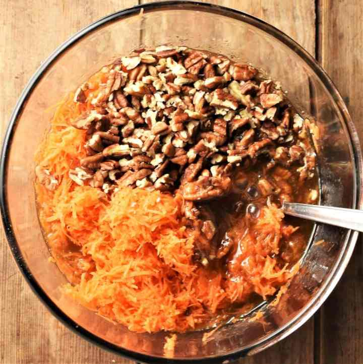Grated carrot and chopped pecans in mixing bowl with spoon.