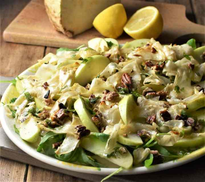 Side view of celeriac apple salad on large plate with lemon in background.