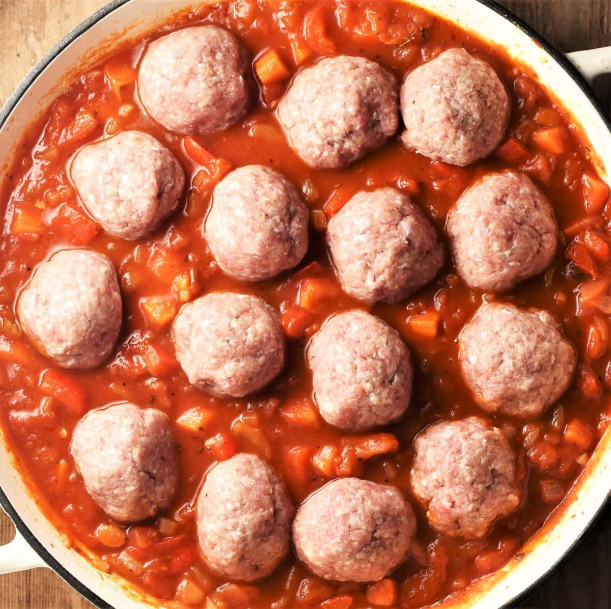 Raw meatballs in chunky tomato sauce in large pan.