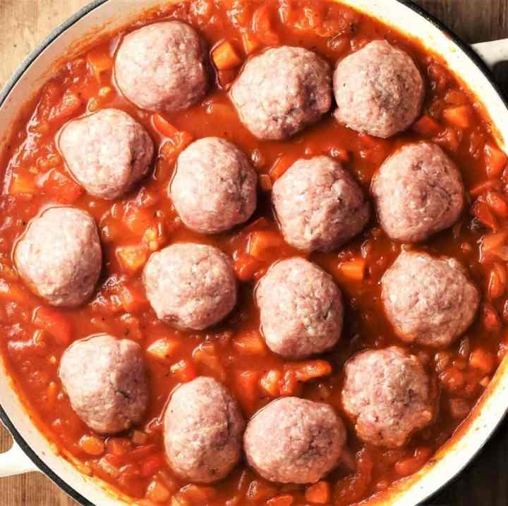 Raw meatballs in chunky tomato sauce in large pan.