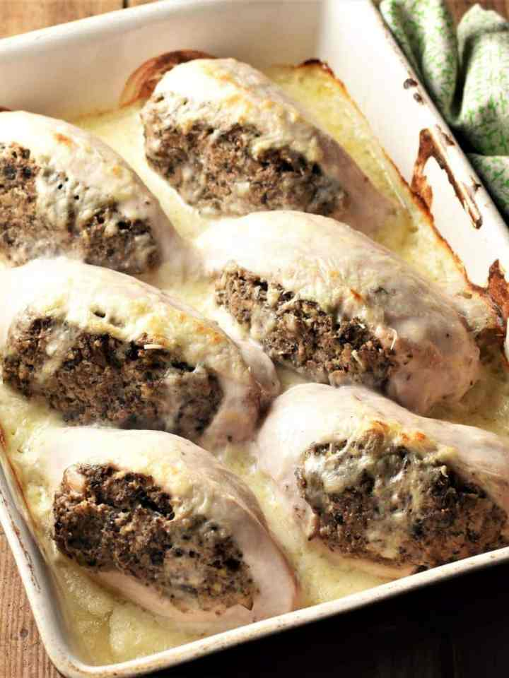 Side view of 6 mushroom stuffed chicken breasts in creamy sauce.