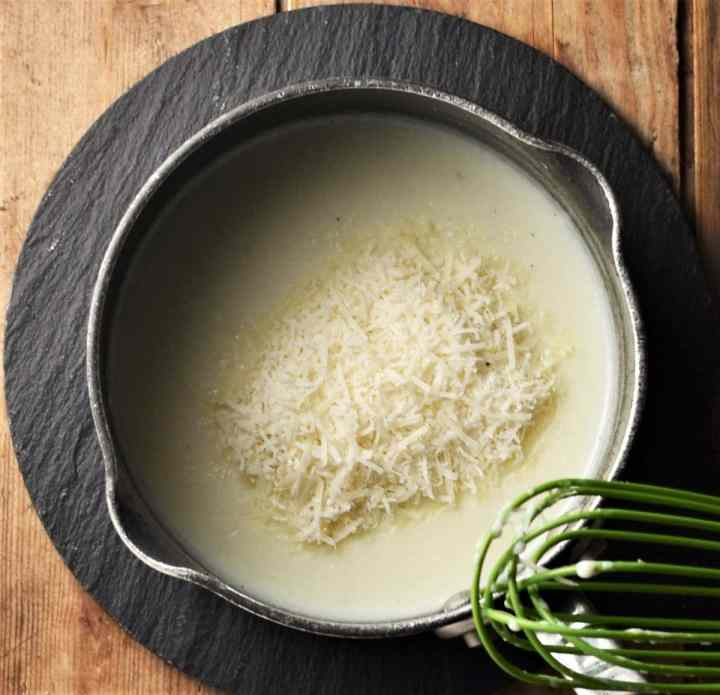 Creamy sauce with grated cheese and whisk in saucepan.