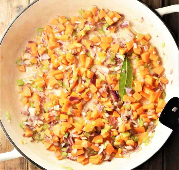 Chopped vegetables in large white pan.