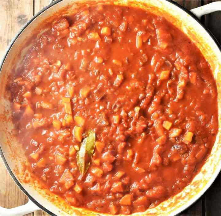 Tomato vegetable sauce in large white pan.