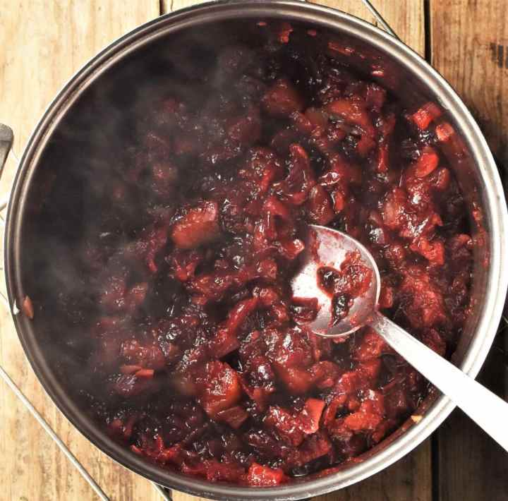 Cooking cranberry chutney in pot with spoon.