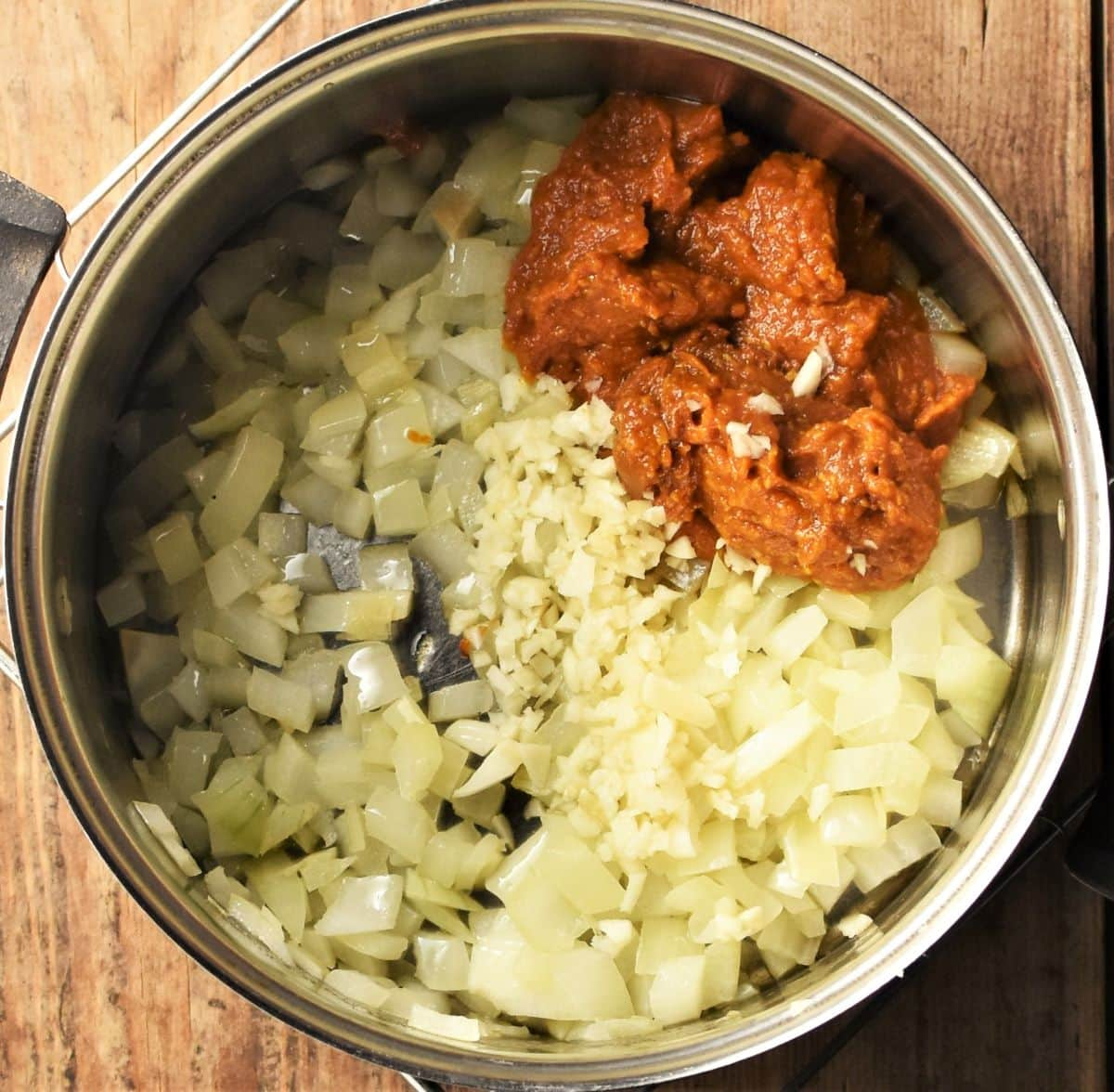 Chopped onion and curry paste in saucepan.