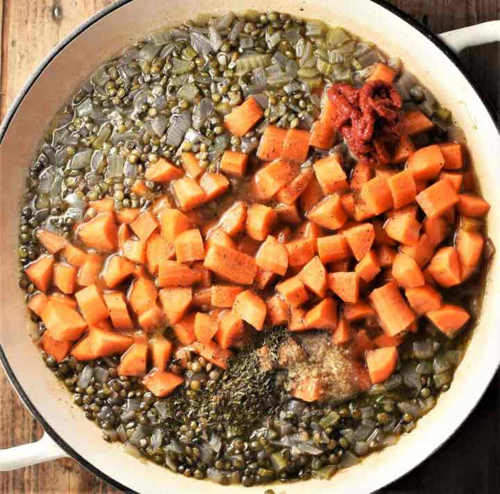 Cooking puy lentils and cubed carrots.
