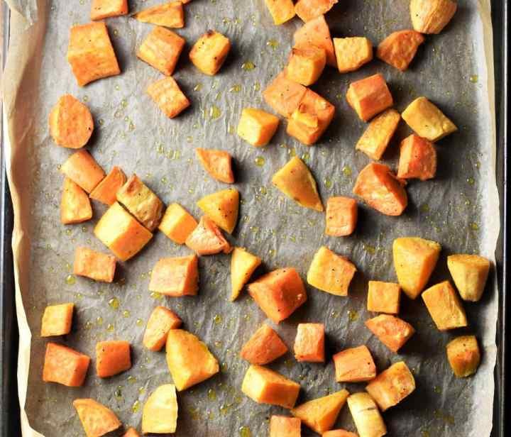 Cubed roasted sweet potato on top of tray lined with parchment.