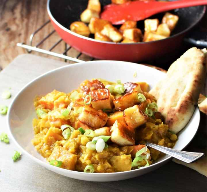 Side view of dhal with sweet potato and halloumi and naan in white bowl with spoon and halloumi cubes in pan in background.