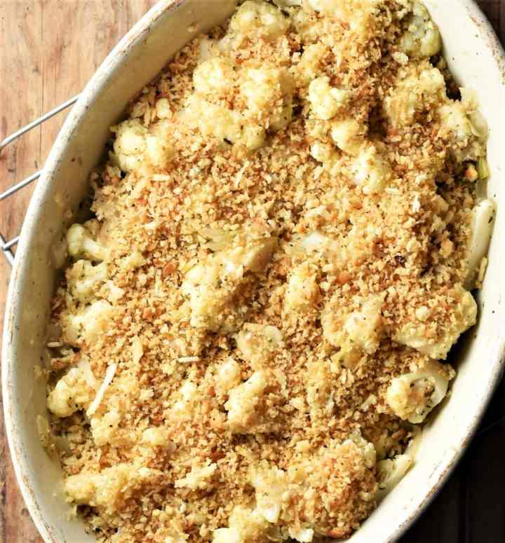 Top down view of cauliflower stuffing with breadcrumb topping in white oval dish.