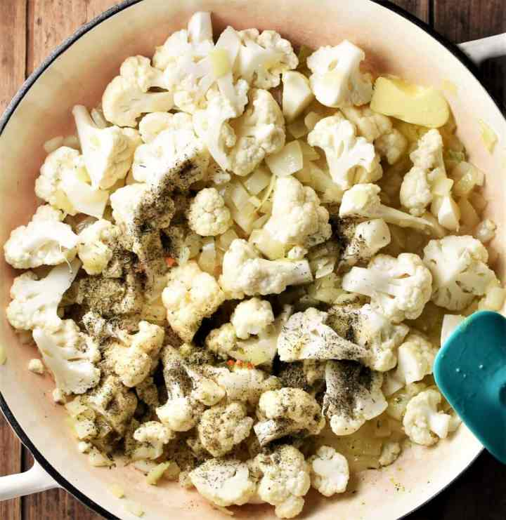 Making cauliflower stuffing mixture in large white pan.