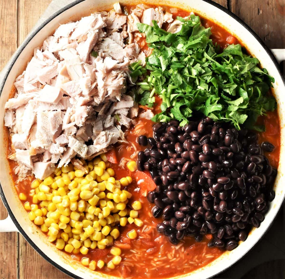 Chopped turkey, black beans, corn, herbs and tomato mixture in large pan.
