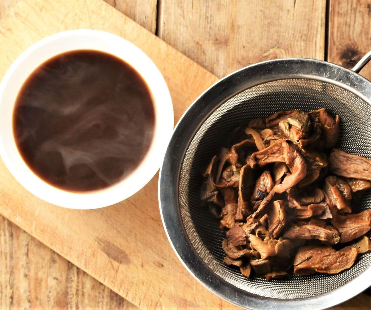 Mushroom broth and cooked mushrooms in sieve.