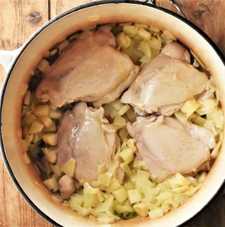 4 skinless chicken thighs with diced vegetables in pot.