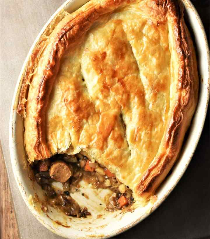 Top down view of sausage pie with puff pastry in oval dish.