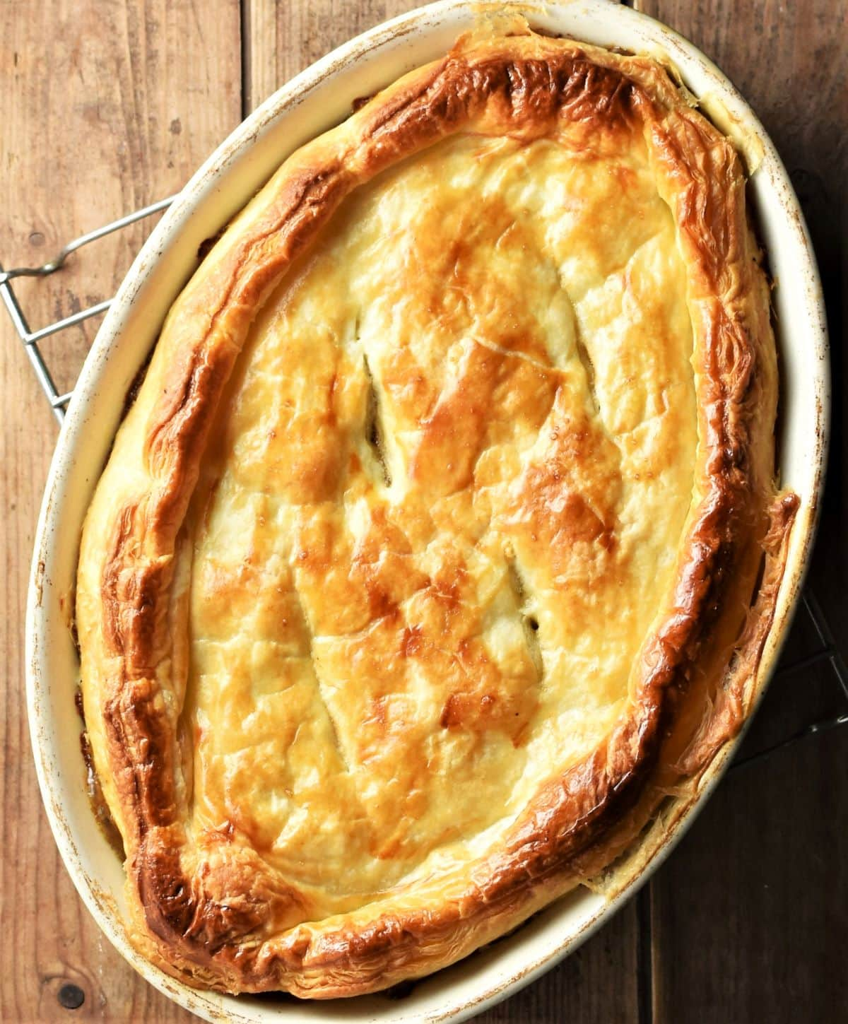 Top down view of pie with golden brown pastry in oval dish.