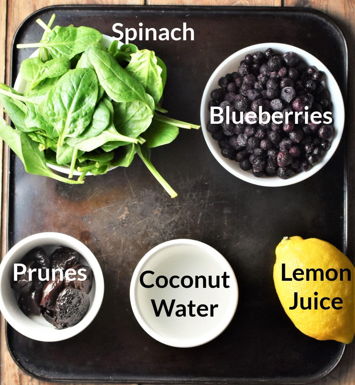 Ingredients for making spinach and blueberry smoothie in individual dishes.